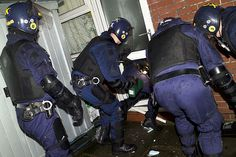 Officers of Greater Manchester Police's Tactical Aid Unit enter a house during a recent police operation. The unit provides the Force with a wide range of specialist services from effective unarmed entry (EUE) and specialist searches, to public order policing and house to house enquiries.    For information about Greater Manchester Police please visit our website.  www.gmp.police.uk