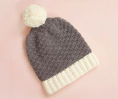 Learn how to make your own cute crochet beanie with this free slouchy shell crochet hat pattern! This pattern features a ribbed brim, shell stitch body, and fluffy pom pom topper.