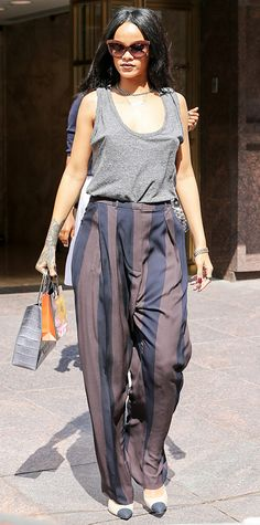 After making a flirty statement in a fuchsia dress, Rihanna did a 180 and stepped out in a decidedly more masculine ensemble in a relaxed gray Alexander Wang tank and striped Haider Ackermann wide-leg trousers. She gave her look a ladylike touch with a miniature Balenciaga handbag and two-toned pumps. #InStyle