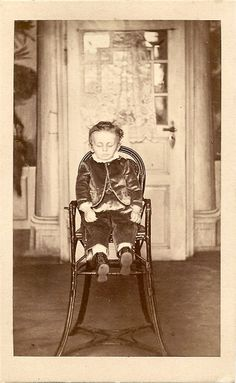 Boy in velvet suit posed in a chair