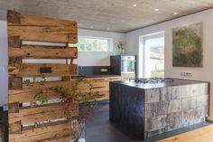 Wohnküche mit Kochblock in warm geschmiedetem Stahl, Altholz, Naturstein