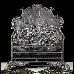 12384: A substantial antique cast iron fire basket with a highly ornate scrolling backplate depicting an Hellenistic battle scene possibly one of AlexanderThe Great's campaign battles. The two barred basket
