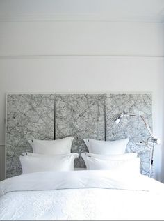 just paste your maps to foam insulation boards, put a couple coats of Mod Podge on top, and hang them together as a headboard at the head of your bed.