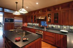 Honed black granite counters with shaker-style cherry cabinets.