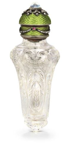 RUSSIAN JEWELLED GOLD AND SILVER-GILT MOUNTED ROCK-CRYSTAL SCENT BOTTLE MARKED FABERGÉ, WITH WORKMASTER'S MARK OF MICHAEL PERCHIN, ST. PETERSBURG, CIRCA 1890. The tapering rock-crystal body is finely carved with foliate scrolls and rocaille, the hinged cover is guilloché enameled in green and applied with rose-cut diamond and ruby-set swags, with a moonstone finial.