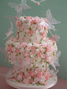 Multi-tiered wedding cake with pink sugar paste flowers all around and gossamer pink butterflies fluttering about.