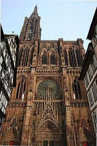 "Strasbourg Cathedral or the Cathedral of Our Lady of Strasbourg  Described by Victor Hugo as a ""gigantic and delicate marvel"",[6] and by Goethe as a ""sublimely towering, wide-spreading tree of God"",[2] the cathedral is visible far across the plains of Alsace and can be seen from as far off as the Vosges Mountains or the Black Forest on the other side of the Rhine. Sandstone from the Vosges used in construction gives the cathedral its characteristic pink hue."