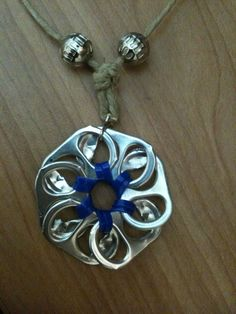 This fun pop tab flower pendant doesn't require too much material and is very easy to make!  Tutorial by Tatiana Ambrose