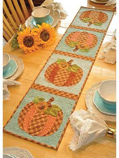 "Celebrate the start of the harvest season with this beautiful table runner! Your kitchen decor will be complete once you deck it out with this vintage-inspired runner that features pretty patchwork pumpkins. You can even use each individual pumpkin to make matching place mats! Finished size is approximately 12 1/2"" x 53""."