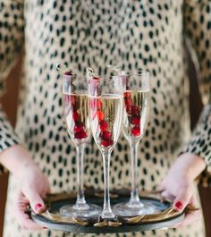 I love this idea from the blog Waiting on Martha:  Use skewers of frozen cranberries to keep your drinks cold- wonderful for the holidays and so pretty!