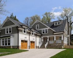 love the gray shingle siding mixed with the white board & batten siding and the lights over the garage doors (which should be imo white wood) are perfect