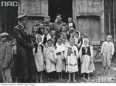 Otto von Wachter (in uniform) and the teacher with the group of barefoot Ukrainian children in front of the wooden school building. Part of the children dressed in folk costumes. 1940-10.