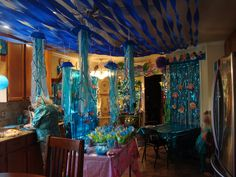 Under the Sea birthday party - ceiling of dining room and jellyfish hanging from ceiling.  Need blue plastic soup bowls, teal, blue, white & green streamers, 2 shades of plastic blue for tablecloth