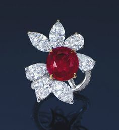 A MAGNIFICENT RUBY AND DIAMOND RING, BY JAMES W. CURRENS FOR FAIDEE  SET WITH AN OVAL-SHAPED RUBY WEIGHING APPROXIMATELY 8.88 CARATS, JOINED BY PEAR AND MARQUISE-CUT DIAMONDS WEIGHING FROM 1.22 TO 1.01 CARATS, TO THE BRILLIANT-CUT UNDULATING HOOP, MOUNTED IN PLATINUM AND 18K YELLOW GOLD, RING SIZE 5¼, IN BLACK FAIDEE CASE