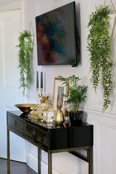 grey dining room with black and gold console and TV on wall