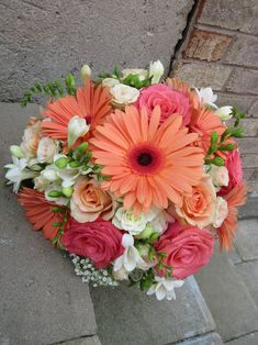 Wedding bouquet of freesia, roses, gerbera daisies and baby's breath in coral, peach and white shades. Designed by Brittany