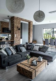 Open spaced grey living room with brick walls and raw wooden table.