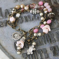 This triple-strand bracelet is dangling with all things pink. Beads include a mix of faceted Pink Jade beads, vintage pearls, vintage pink milk glass pods and flowers, vintage rosary beads, a multitude of faceted Czech glass beads and wonderful old rhinestone findings and rondelles. Among the charms on this bracelet is a vintage sterling silver religious medal and a rhinestone bauble. Bracelet can be sized especially for your wrist.