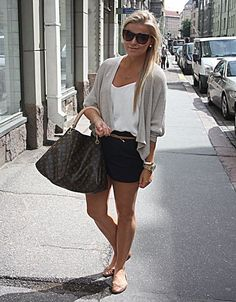 Keep it ladylike and elegant. Go for a beige wrap cardigan, loose-fit white top, black chino shorts, ballerina flats and designer bag.