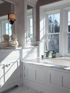 Recessed panel cabinetry and tub surround painted pristine white and topped by marble counter tops and tub decking in this classic bath