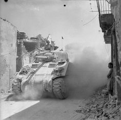 A Canadian Sherman tank passes through a bomb scarred street in Regalbuto, Sicily. 4 August 1943. (IWM)