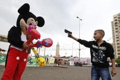A Syrian refugee boy points a plastic toy pistol at a man in a Mickey Mouse costume on the first day of Eid al-Adha at a park in Beirut, Lebanon October 26, 2012.  REUTERS/Jamal Saidi Mickey Mouse Costume, Minnie Mouse, Powerful Images, Most Powerful, Eid Al-adha, Syrian Refugees, Recent Events, Old Toys, Photojournalism