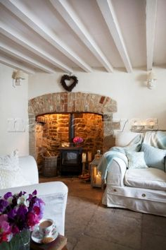 Wood burning stove and slip covered threepiecesuite in whitewashed living room of Corfe Castle cotta