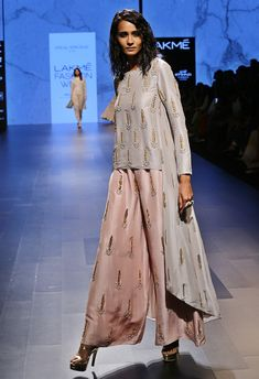 A dove grey dupion high-low silk tunic with gold leaf motif zardozi embroidery all over and embellished with pearls. It is paired with a blush pink silk palazzo pants with gold embroidered feather motifs. PS
