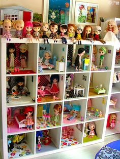 Using a bookshelf as a dollhouse  These dolls are creepers but I like the idea.