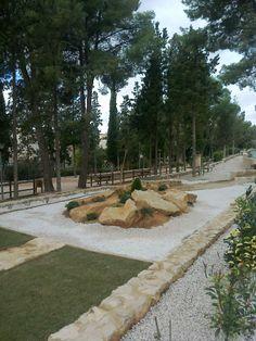 Vista del jardín de rocalla con vía y césped desde muro.