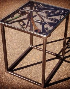 One of the coolest end stands I have ever seen! Metal art sculpture and furniture all wrapped into one! Vintage tools welded into the table top to look like they are floating and finished with slab glass.