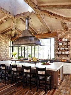 The smart island in the home's open-layout kitchen serves double-duty as a cooking center and dining area. A 15-foot marble-slab top adds sophistication, while a pendant lighting fixture adds industrial edge. #industrialkitchens