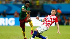 Ivan Perisic of Croatia controls the ball as Dany Nounkeu of Cameroon gives chase. Wearing blue kinesiology tape on his forearm.