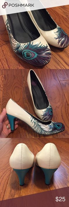 Peacock Feather Pumps Cream colored heels with a teal and purple peacock feather on each shoe. Heel itself is teal. Comfortable, worn 3-4xs, few black scuff marks on inside front (photo 4). t. u. k. Shoes Heels