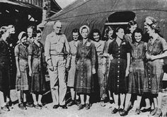 LIBERATED NURSES, wearing dresses they made while interned in Jap prison camp, welcomed back to safety of U.S. base by Vice Admiral Kinkaid ~