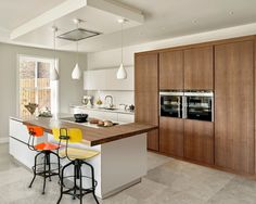 Wimbledon kitchen in Walnut and Cornforth white. Walnut kitchen cabinets with wall mounted ovens. Two-tier island with breakfast bar, integrated hob and teardrop pendant lighting.