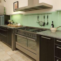 Limestone floor, stainless range (with stainless side pillars), green splashback.  NB floor tiles not laid in lines ...