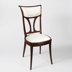 Eugène Gaillard, featuring detailed carvings of acanthus leaves scrolling up the sides, with a contemporary Art Nouveau-design silk fabric. A similar chair is pictured in: The Paris Salons, 1895-1910