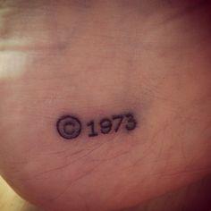 Pequeño tatuaje en el pie, cerca del talón, con el símbolo del Copyright y el número 1973