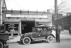 """Automobile, repairman and driver in front of repair and used car shop in Washington, D.C. Notice the window printing """"alcohol for sale for automobiles"""" c. 1920"""
