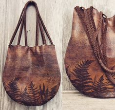 Woodland Fern leather bag made from a unique, embossed leather, with ferns and wood grain. The bag is 15 tall by 14 wide. Fully lined with 2, drop in, leather pockets. The double straps on the bag are made from skinny braided leather and wrapped at the top. The straps have a 13 drop. Hand stitched, top scalloped rim. Magnetic snap closure.