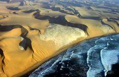 desert meets ocean, sea brushing against the dunes of the Namib desert