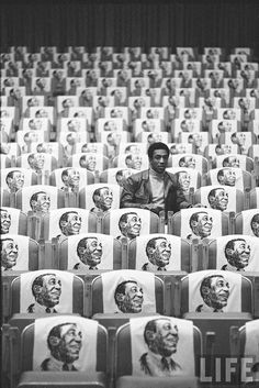 Bill Cosby sitting in empty auditorium filled with copies of his likeness on each seat, Las Vegas by Michael Rougier. 1968