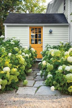 Get creative with door color. Yellow Marigold in Aura® Grand Entrance® in a satin sheen completes this garden. Best Exterior House Paint, White Exterior Paint, White Exterior Houses, Exterior Paint Colors, Exterior House Colors, Exterior Doors, Exterior Design, Bungalow Exterior, Exterior Trim