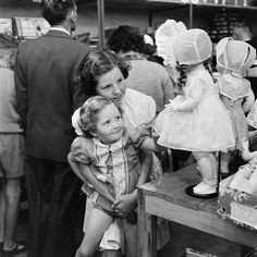 Little girl looking at dolls with emotional eyes      Shop Window, Paris, 1947      Store window of a doll shop, ca. 1920s      A little g...