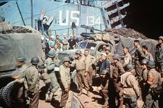 Trucks of the 1st Infantry Division of the United States Army are loaded into a Landing Ship Tank (LST) in Dorset, United Kingdom, on June 5th, 1944