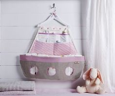 "Fabric boat - changing table storage:- Keep baby's nursery organized with our beautiful fabric boat .   Hang pink boat on the wall near the changing table , where it holds diapers and other essentials at the ready.    The details make the difference:   * 6 pockets for a convenient storage.  * 20"" x 25"" (50x64cm) - Larg size for your convenience.  * Decorated with chic nautical colors. A great way to welcome the new baby home.  * Use to store baby's essentials for changing time.  Price: $79"