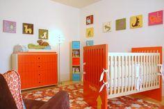 lit de bébé en orange, peinture blanc neige, tapis graphique et cadres décoratifs multicolores