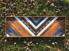 Reclaimed Geometric Wood Art. Each piece is stained, cut, and arranged to create an eye-catching pattern to enhance any space. Perfect for a housewarming, anniversary, Christmas, wedding, or birthday gift! • Piece measures approximately 12 x 36 inches. • Hanging hardware included.