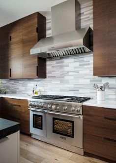 Designed for maximum durability, this modern kitchen by Kristianne Watts includes rich walnut cabinets, Silstone countertops and sleek, stainless appliances. A small island and rustic dining table ensure plenty of spaces to eat and entertain.